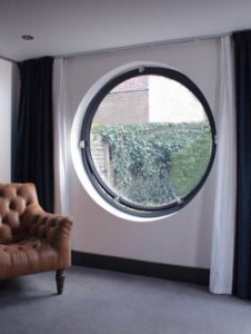 Large open circular aluminium window with curtains and chair