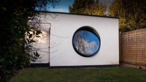 Large open circular aluminium window in wall of white building