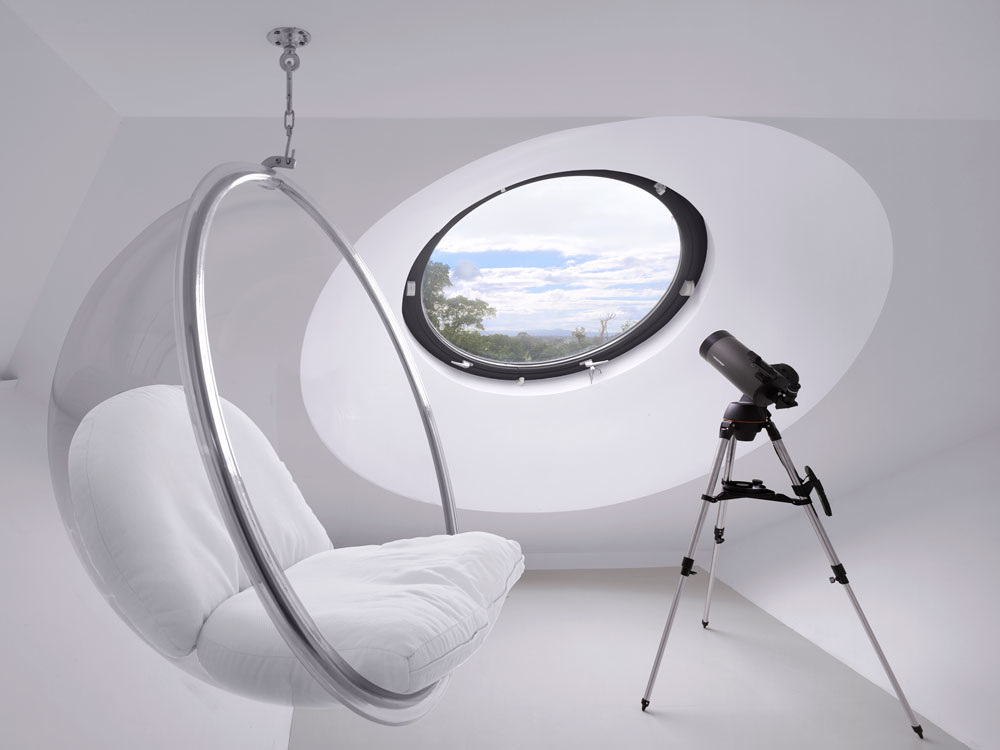 Contemporary room with hanging seat and large round aluminium window